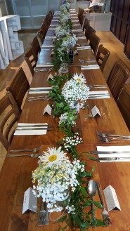 The Daisy and Gypsophila theme carried on through to the wedding breaksfast table with a table runner of foliage.