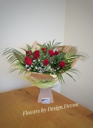 £50. Happy 10 year anniversary bouquet. 10 red roses with spray carnations, palm and pittosporum