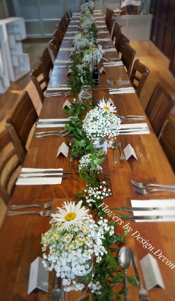Table decoration. Foliage garland and posies of Daisy and Gypsophila